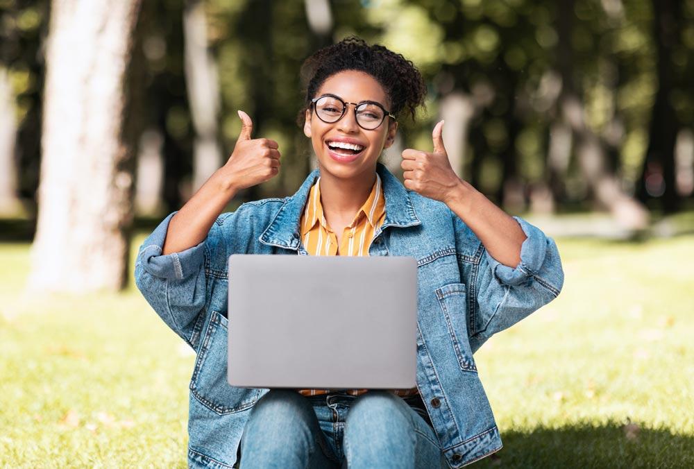 Jente med bærbar pc holder begge tomlene opp, bilde.
