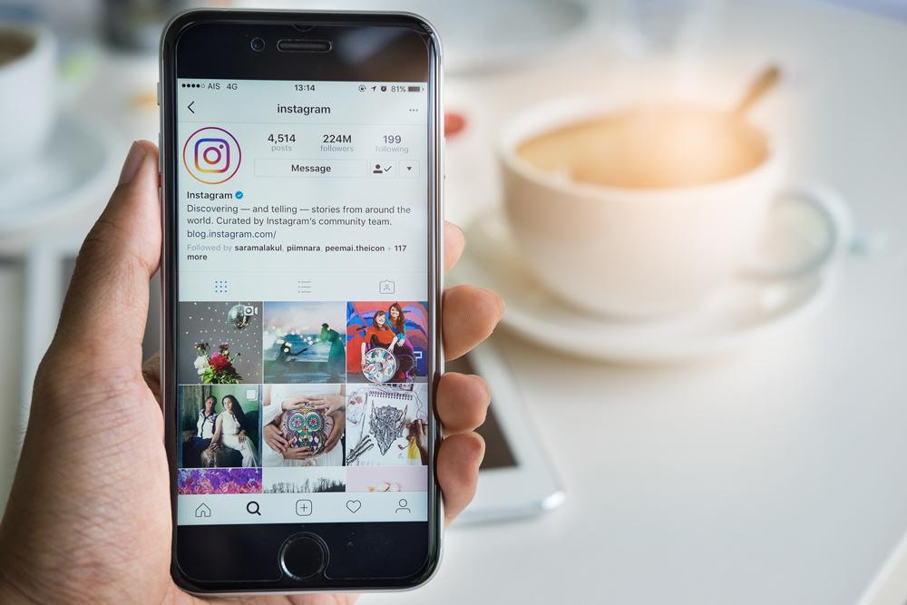 Hånd holder telefon med instagram på skjermen. Kaffekopp i bakgrunnen. Bilde.